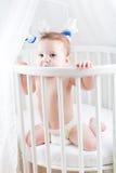 Bebé divertido que se sienta en un pesebre blanco redondo fotos de archivo