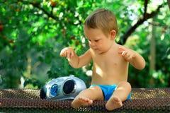 bebé DJ que juega con el registrador retro en el jardín, sentándose Imágenes de archivo libres de regalías
