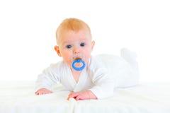 Bebé doce com o soother que coloca no tecido Fotografia de Stock