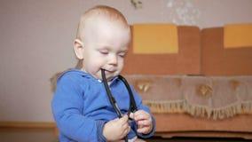 Bebé dulce con el estetoscopio en casa El niño mastica los dientes del aparato médico almacen de video