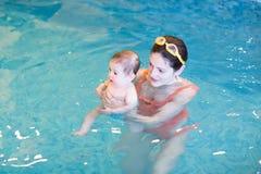Bebé dulce con su madre en clase temprana de la natación imagenes de archivo