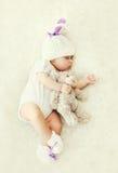 Bebé dulce que duerme con el juguete del oso de peluche en el hogar suave blanco de la cama Fotografía de archivo
