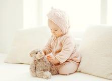 Bebé dulce que juega con el juguete del oso de peluche en casa en el sitio blanco Imagen de archivo libre de regalías
