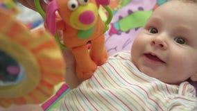 Bebé dulce que juega el juguete Ciérrese para arriba del bebé lindo que miente en la estera colorida almacen de metraje de vídeo