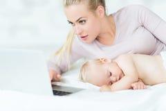 Bebé durmiente al lado de la madre que usa el ordenador portátil Fotografía de archivo