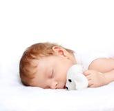 Bebé durmiente con el juguete Fotos de archivo libres de regalías