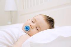 Bebé durmiente con el pacificador Fotos de archivo libres de regalías