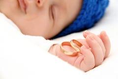 Bebé durmiente con los anillos de bodas Imagen de archivo
