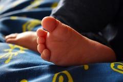 Bebé durmiente descalzo en la hoja azul con los soles amarillos imagen de archivo libre de regalías