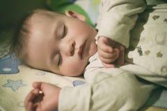 Bebé durmiente en cama Fotos de archivo libres de regalías