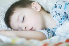 Bebé durmiente en cama Imagenes de archivo
