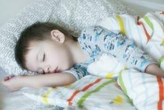 Bebé durmiente en cama Imagen de archivo