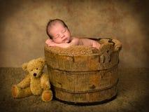 Bebé durmiente en cubo antiguo imagen de archivo libre de regalías