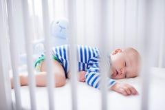 Bebé durmiente en el pesebre blanco Imagen de archivo