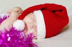Bebé durmiente en el sombrero del Año Nuevo entre la lentejuela Foto de archivo libre de regalías