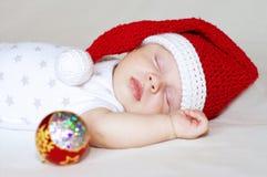 Bebé durmiente en el sombrero del Año Nuevo y la decoración del árbol de navidad Imagen de archivo libre de regalías