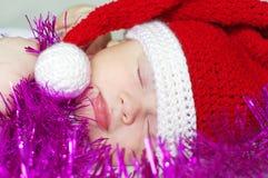 Bebé durmiente en los regalos que esperan del sombrero del Año Nuevo Foto de archivo libre de regalías