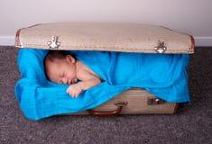 Bebé durmiente en maleta Imagen de archivo libre de regalías