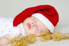 Bebé durmiente precioso en un sombrero del Año Nuevo Fotografía de archivo