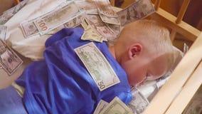 Bebé durmiente y dinero que cae Riqueza inesperada del concepto almacen de metraje de vídeo