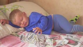 Bebé durmiente y dinero que cae Riqueza inesperada del concepto Un triunfo grande almacen de video