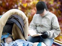 Bebé durmiente y lectura del padre Foto de archivo libre de regalías