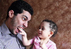 Bebé egipcio árabe que juega con su padre imagen de archivo