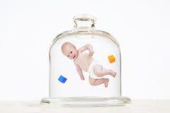 Bebé, elevando y manteniendo flotando en un tarro de cristal Fotografía de archivo