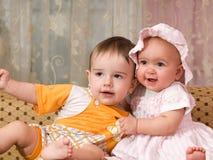 Bebé em uma cor-de-rosa e um rapaz pequeno Imagens de Stock Royalty Free