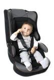 Bebé en asiento de coche sobre blanco Foto de archivo libre de regalías