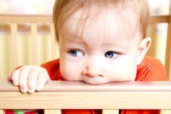 Bebé en Bitting en el pesebre Imagenes de archivo