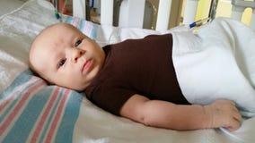 Bebé en cama de hospital Imagen de archivo