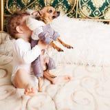 Bebé en casa que juega con el perro Imagen de archivo libre de regalías