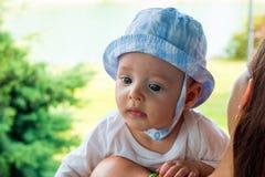 Bebé en casquillo en poca cabeza con la cara fascinada y los ojos azules enfocados que descansan sobre exterior del hombro de los imagen de archivo libre de regalías