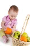 Bebé en color de rosa y frutas Imagen de archivo