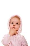 Bebé en dedo rosado en la boca que mira para arriba Foto de archivo