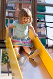 Bebé   en diapositiva en el área del patio Fotos de archivo