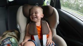 Bebé en el asiento de carro del ` s de los niños en el coche Embrome las sonrisas, las risas y las ondas sus manos feliz imágenes de archivo libres de regalías