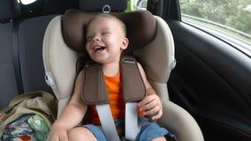 Bebé en el asiento de carro del ` s de los niños en el coche Embrome las sonrisas, las risas y las ondas sus manos feliz fotos de archivo