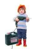 Bebé en el casco de protección con el taladro y la caja de herramientas Imagen de archivo
