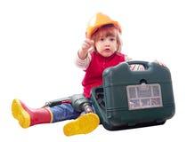 Bebé en el casco de protección con las herramientas de funcionamiento Imagen de archivo