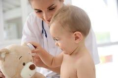 Bebé en el doctor con el oso de peluche Fotografía de archivo libre de regalías