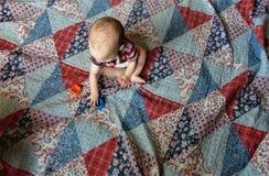 Bebé en el edredón de remiendo multicolor foto de archivo
