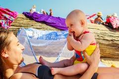 Bebé en el estómago de la mujer en la playa Foto de archivo