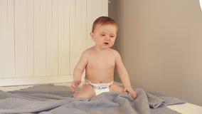 Bebé en el pañal que juega y que sonríe mientras que se sienta en una manta metrajes