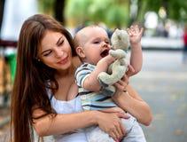 Bebé en el parque al aire libre Embrome con el juguete en las manos del ` s de la mamá Fotos de archivo libres de regalías