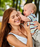 Bebé en el parque al aire libre Niño en las manos del ` s de la mamá Imagen de archivo libre de regalías