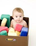 Bebé en el rectángulo de juguetes Imagenes de archivo