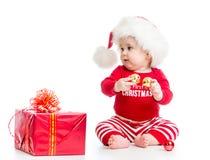 Bebé en el sombrero de Papá Noel con la caja de regalo de la Navidad aislada Imagen de archivo libre de regalías