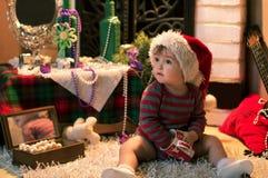 Bebé en el sombrero de Papá Noel que se sienta en la alfombra con un casquillo Fotos de archivo libres de regalías